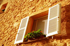 French window with white shutters. Window with shutters on a warm afternoon, French Riviera Royalty Free Stock Images