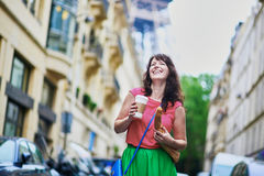 French woman walking with coffee to go and baguette Royalty Free Stock Photo