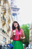 French woman walking with coffee to go and baguette on a street of Paris Stock Image
