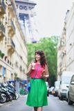 French woman walking with coffee to go and baguette on a street of Paris Royalty Free Stock Photos