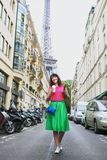 French woman walking with coffee to go and baguette on a street of Paris Royalty Free Stock Images