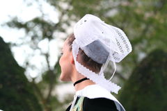 Traditional embroidered breton lace hat. French woman wearing traditional embroidered breton lace hat stock image