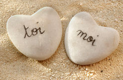 French you and me hearts of pebbles in the sand Royalty Free Stock Image