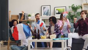 French young people fans watching sports on TV waving flags enjoying game. French young people excited fans are watching sports on TV waving national flags of stock footage