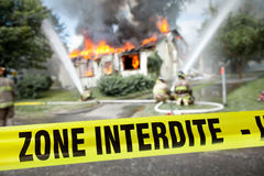 French Zone Interdite tape with firefighters and a burning house. In the background Royalty Free Stock Photography