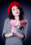 Frenchwoman with pink spiral lollipops. Beautiful young Frenchwoman with pink spiral lollipops Stock Photography