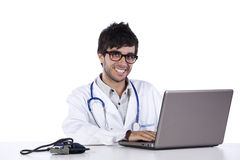 Frendly junger Doktor, der an seinem Laptop arbeitet Stockbild