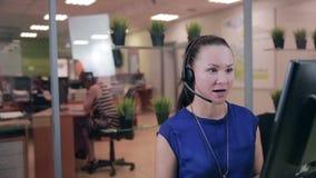 Frendly kvinna som talar på hörlurar med mikrofon i ett ljust rent kontor, appellmitt