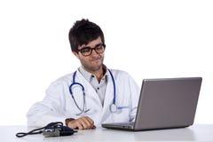 Frendly ung doktor som fungerar med hans bärbar dator Arkivfoto
