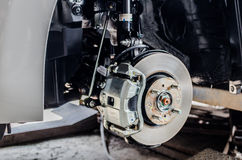 Freno a disco anteriore sull'automobile in corso di nuova sostituzione del pneumatico Fotografia Stock