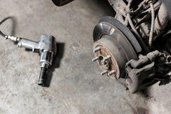 Freno a disco del primo piano del veicolo per la riparazione ruota del colpo, lo strumento per l'allentamento dei dadi vite inter Fotografia Stock Libera da Diritti