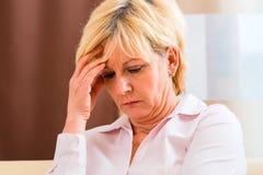 Frente conmovedora mayor que tiene dolor de cabeza o dolor Foto de archivo libre de regalías