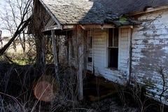 Frente de una casa de marco blanca abandonada vieja Foto de archivo