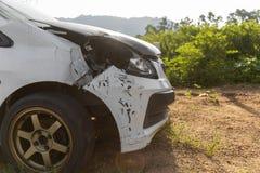 Frente del parque dañado y accidentalmente roto blanco del coche del color en el camino con el espacio de la copia para el texto  imagen de archivo