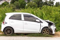 Frente del parque dañado y accidentalmente roto blanco del coche del color en el camino fotografía de archivo