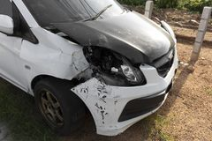 Frente del parque dañado y accidentalmente roto blanco del coche del color en el camino fotos de archivo