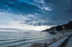 Frente marítima no por do sol com nuvens de chuva Fotos de Stock Royalty Free