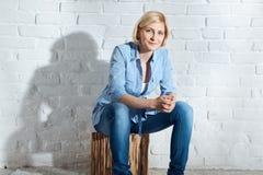 Frente que se sienta de la mujer casual de la pared de ladrillo blanca Foto de archivo