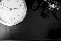 The frenzy of today`s times in contrast with the past. A modern design wall clock next to a vintage camera on a black background royalty free stock photography