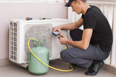 Freon air conditioner refill. Master of repair air conditioners at work Royalty Free Stock Image