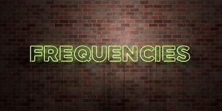 FREQUENCIES - fluorescent Neon tube Sign on brickwork - Front view - 3D rendered royalty free stock picture Stock Photo