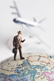 Frequent flier. Business figurine on earth globe with toy airplane in background Royalty Free Stock Photo