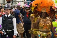 Frequentatore & poliziotto di carnevale al carnevale del Notting Hill fotografia stock libera da diritti