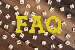 Frequently asked question FAQ with question mark tiles. FAQ word on blurred wooden background. FAQ concept Royalty Free Stock Photo