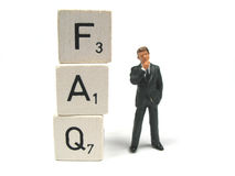 Frequently asked questions. A man stand beside frequently asked questions royalty free stock photo