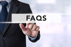 Frequently Asked Questions Faq Feedback  Concept. Businessman hands touching on virtual screen and blurred city background Stock Photo