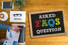 Frequently Asked Questions Faq Feedback Concept. Businessman working at office desk and using computer and objects, coffee stock image