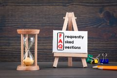 Frequently asked questions. Sandglass, hourglass or egg timer on wooden table. Showing the last second or last minute or time out Royalty Free Stock Image