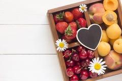 Fresa, cereza dulce y albaricoques en una caja de madera Imágenes de archivo libres de regalías