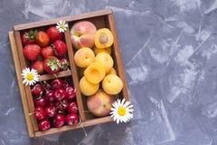 Fresa, cereza dulce y albaricoques en una caja de madera Foto de archivo libre de regalías