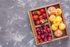 Fresa, cereza dulce y albaricoques en una caja de madera Fotos de archivo