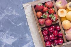 Fresa, cereza dulce y albaricoques en una caja de madera Imagenes de archivo