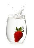 Fresa en el vidrio de agua con el chapoteo Imagenes de archivo