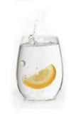 Fresa en el vidrio de agua con el chapoteo Imagen de archivo