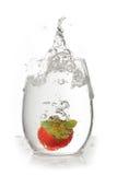 Fresa en el vidrio de agua con el chapoteo Fotografía de archivo