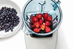 Fresa en licuadora con los ingridients para el smoothie en el CCB blanco foto de archivo libre de regalías