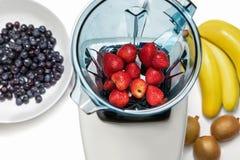 Fresa en licuadora con los ingridients para el smoothie en el CCB blanco imagenes de archivo