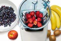 Fresa en licuadora con los ingridients para el smoothie en el CCB blanco fotos de archivo