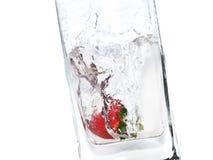 Fresa en un chapoteo transparente del agua en un vidrio Imagen de archivo libre de regalías