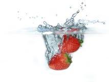 Fresa fresca caída en el agua Imagen de archivo libre de regalías