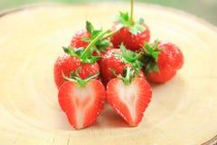 Fresa fresca, frutas, entero dulces y corte por la mitad, en la tajadera de madera Foto de archivo