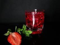 Fresa, menta, hielo, bebida en un fondo negro fotos de archivo