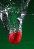 Fresa que cae en agua Fotografía de archivo