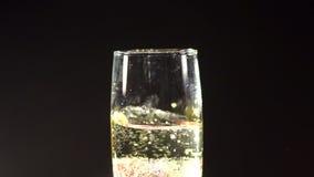 Fresa que cae en un vidrio de champán en oscuridad metrajes
