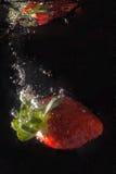 Fresa que salpica en agua Imágenes de archivo libres de regalías