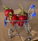Fresa roja en una carretilla de las compras Imagen de archivo